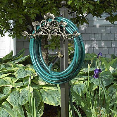 Dekorativ trädgårdsslanghållare med förlängning av kran utomhus.