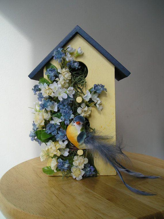 Inomhus dekorativt handmålat fågelhus med blå fågel och blått.