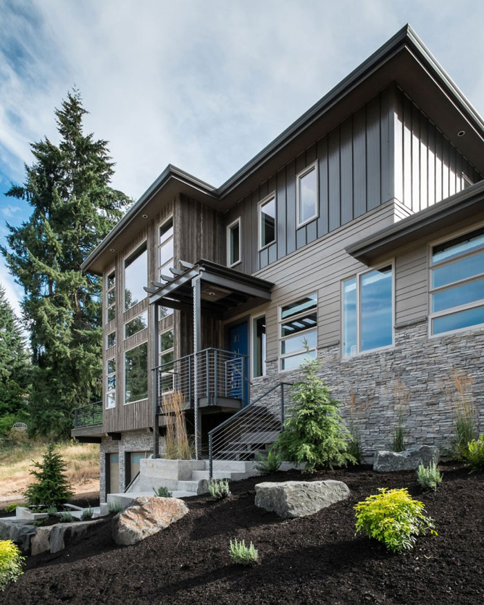 82285398265 Hus med natursten och trä exteriör och en avancerad interiör