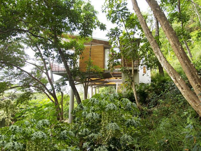 82975031676 Modernt hus med många träelement i sluttningen