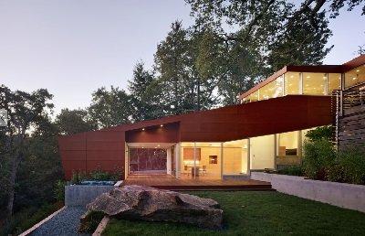 Modernt hus byggt på en sluttning med massor av träelement